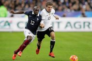 Thomas Mueller of Germany (roentgen) is challenged by France's Lassana Diarra (L) at Stade de France.